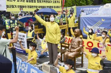 1日、ソウルの日本大使館前に設置された従軍慰安婦の被害を象徴する少女像前で座り込む革新系の団体。奥は横断幕を掲げる保守系団体(共同)