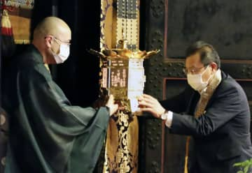 比叡山延暦寺の僧侶(左)に戻される全国行脚する予定だった灯籠=1日午後、大津市