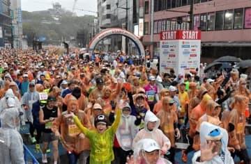今年2月の熊本城マラソンで、雨の中、熊本城をバックにスタートするフルマラソンのランナー=熊本市中央区の通町筋電停前