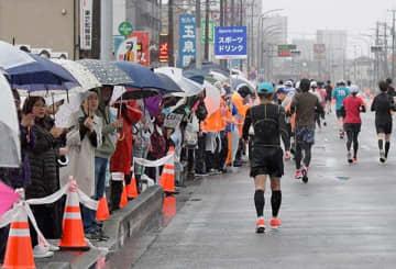 今年の熊本城マラソンで、雨の中、力走するランナーを応援する人たち=2月16日、熊本市西区(小野宏明)