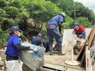 孤立状態が続いていた白石地区で災害ごみの搬出作業に当たる地元の消防団員ら=1日午前、芦北町