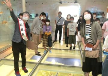 県立環境と人間のふれあい館「一日館長」の高橋なんぐさん(左)と展示を見る子どもたち=1日、新潟市北区