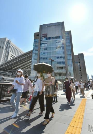 強い日差しの中、マスク姿でJR大阪駅前を歩く人たち=2日午後2時49分