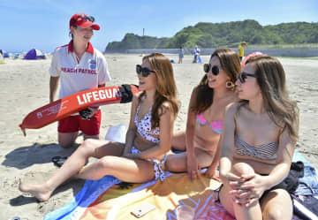水着姿で日光浴を楽しむ女性たち=2日午後、福島県いわき市の薄磯海岸