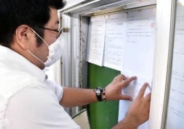 住民投票の告示文書を掲示する垂水市職員=市役所