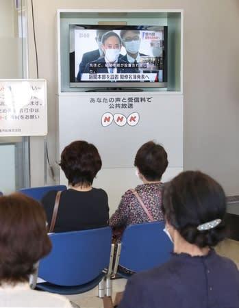 佐渡汽船の待合室で新内閣発足のテレビ中継を見る乗客=16日、新潟市中央区