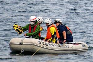 ボートから水中ドローンを猪苗代湖に放つ参加者