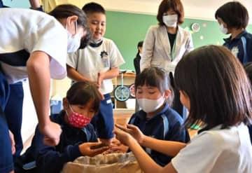 出来上がった堆肥を手に取る児童ら