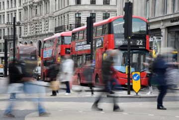 ロンドン中心部、オックスフォード・サーカスの小売店街を行き交う買い物客ら=16日(ロイター=共同)
