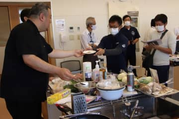 地元産シイラのしゃぶしゃぶを提案し、試食を勧める薄シェフ(左)=平戸市未来創造館