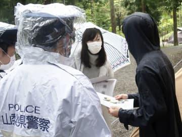行方不明の小倉美咲さんの情報提供を求めるビラを配る母とも子さん=17日午前、山梨県道志村