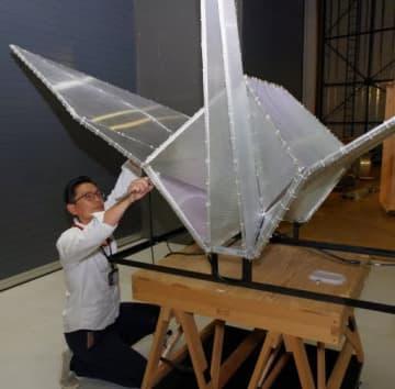 折り鶴オブジェの胴体や羽を組み立てる堀信さん