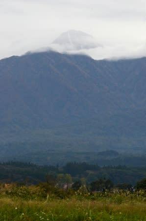 雲の合間から、山頂付近にうっすらと積もった雪が見える妙高山=17日、妙高市