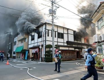 火災現場付近で通行に規制をかける警察官ら=17日午後1時11分、長崎市岩川町