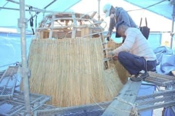 【編んだわら束を骨組みに貼付けていく参加者ら=鈴鹿市深溝町の深溝ライスセンター敷地内で】