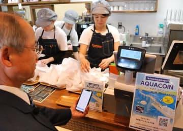 スマートフォンをQRコードにかざし商品を買う君津信組の宮沢理事長=28日、木更津市
