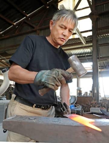 熱した鉄を金づちでたたいて形を整える田中さん=大村市、田中鎌工業