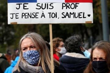 18日、フランス・リールの追悼集会でメッセージを掲げる女性(ロイター=共同)