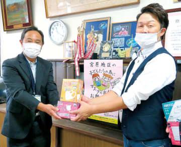 集めたマスクを宮原小学校の佐藤校長に手渡す狩野さん(右)=15日午前、さいたま市北区