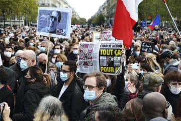 教員殺害テロ事件の追悼集会で、週刊紙シャルリエブドの紙面や犠牲となった教員の写真を掲げた参加者ら=18日、パリ(共同)