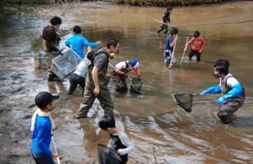 【腰まで泥だらけになり池干し体験をする塾生ら=亀山市椿世町の里山公園「みちくさ」で】