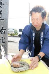 御幣を立て、赤飯のにぎり飯を添えた桟俵を置く祭典委員長の堀正範さん=姫路市大津区北天満町