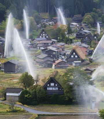紅葉の白川郷で恒例の放水訓練 輝く水柱、合掌造りの火災に備え 画像