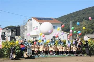 ヒマワリ畑で風船を空に放す子どもたち=熊本市西区