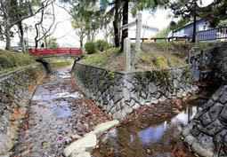 高谷川の境界部分。川の流れが分岐し、「日本海へ約70キロ」「瀬戸内海へ約70キロ」と書かれた看板が立つ=丹波市氷上町石生