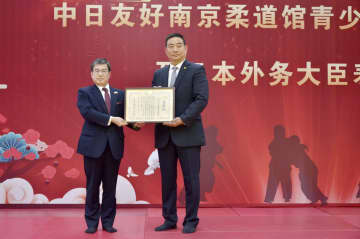 21日、表彰状を受け取る中日友好南京柔道館の劉俊林館長(右)=中国・南京市(共同)