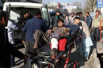 21日、アフガニスタン首都カブールで、ロケット弾が住宅地に着弾し、病院へ運ばれる男性(ロイター=共同)