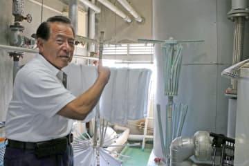 普賢岳噴火災害の避難者が宿泊時に洗濯物を干していた機械室で、当時の様子を説明する町田さん=雲仙市小浜町、旅館山田屋