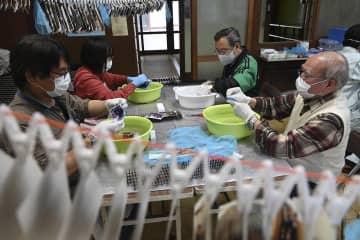 水害に遭った写真を一枚一枚丁寧に洗浄し、乾燥させるボランティア=1日、川崎市高津区