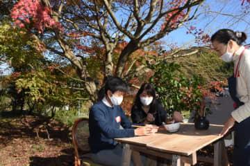 色づく紅葉の下で、絵付け体験も楽しめる。右は陶芸家の土屋由起子さん=唐津市浜玉町の由起子窯