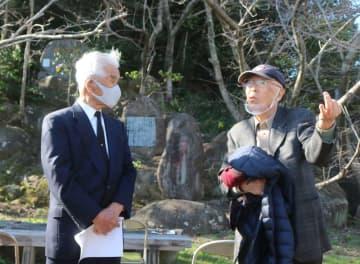 米B29鎮魂碑(左上)の下で語り合う森さん(左)と犬尾さん=諫早市小長井町