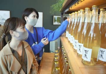 今夏のブドウで造った菊鹿ワイナリー限定販売の新酒「菊鹿シャルドネフレッシュ2020」を手に取る買い物客=山鹿市