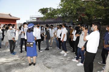 首里城で火災からの再建などについて説明を聞く生徒たち=4日、那覇市(藤代高校提供)
