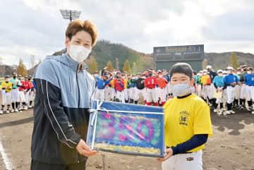 学童野球の選手から、花で打率を示した額を受け取り喜ぶオリックスの吉田正尚選手(左)=11月22日、福井市の福井フェニックススタジアム