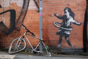 後輪のない自転車を柱につなぎ、外した後輪で少女が遊ぶ構図となっているバンクシーの作品=10月、ノッティンガム(ロイター=共同)