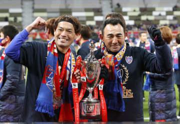 柏に競り勝ち優勝を決め、トロフィーを手に写真に納まるFC東京・東(左)と長谷川監督=国立競技場