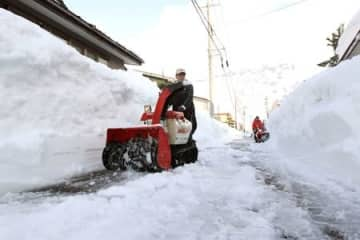 雪に埋もれた住宅街の道路を除雪する男性=13日午後3時すぎ、上越市国府3