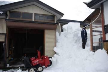 小屋の屋根から落ちてきた雪に埋まった位置に立つ男性