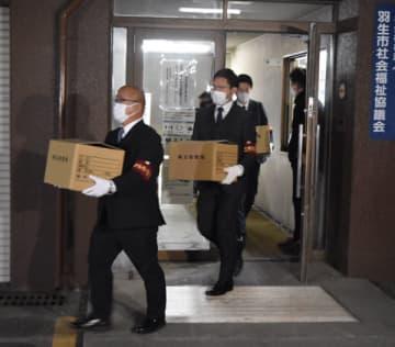 羽生市役所を家宅捜索し、押収品を運び出す県警の捜査員=11日午後8時10分ごろ、羽生市役所