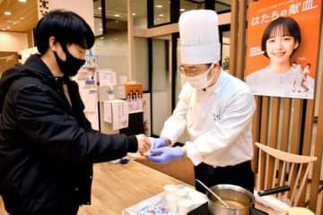献血ルームで中華スープを振る舞う日本中国料理協会県支部の会員(右)