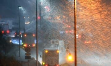 雪が降りしきる中、北陸自動車道上り線の女形谷パーキングエリア付近で立ち往生する車両=1月9日午後8時ごろ、福井県坂井市丸岡町女形谷