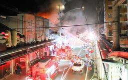 消防車両などが駆け付け、通行止めになった大開通=13日午後6時37分、豊岡市中央町