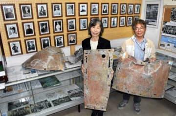 彗星の機体の一部を持つ前田孝子さん(左)ら。後ろに並ぶのは、戦没隊員の遺影=曽於市埋蔵文化財センター