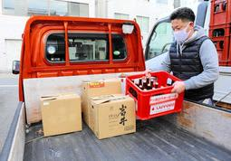 軽トラックの荷台にビール瓶を積み込むすずらん吉田商店の吉田寛さん=神戸市北区鈴蘭台北町1