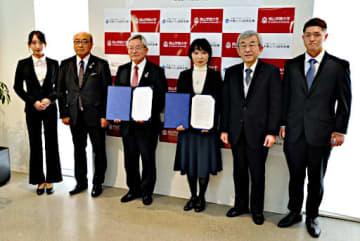協定書への署名を終え、連携をアピールする高橋理事長(左から3人目)、牧野学長(同4人目)ら関係者=18日、大阪市阿倍野区
