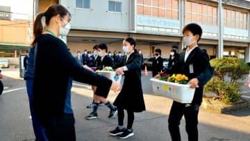 丹精した花の鉢植えを手渡す金子小の児童ら